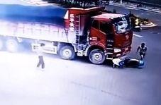 موتور سواری که از زیر چرخهای دو کامیون جان سالم به در برد